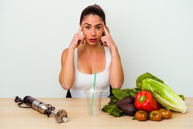 Молодая кавказская женщина, готовящая здоровый коктейль с овощами, сосредоточилась на задаче, держа указательные пальцы, указывая головой.