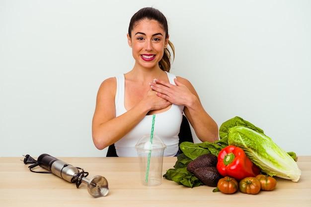 야채와 함께 건강한 스무디를 준비하는 젊은 백인 여자는 가슴에 손바닥을 눌러 친절한식이 있습니다. 사랑 개념.