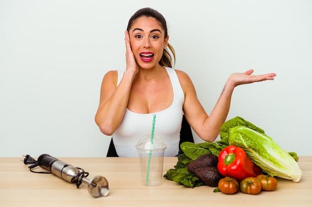 야채와 함께 건강 한 스무디를 준비하는 젊은 백인 여자 손바닥에 복사 공간을 보유 하 고 뺨에 손을 유지합니다. 놀랍고 기뻐했습니다.