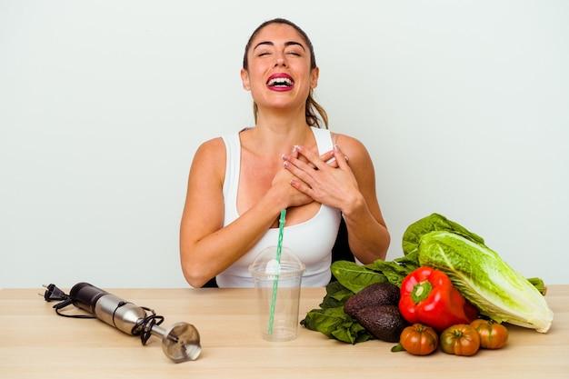 행복의 개념, 마음에 유지 손을 웃 고 야채와 함께 건강 한 스무디를 준비하는 젊은 백인 여자.