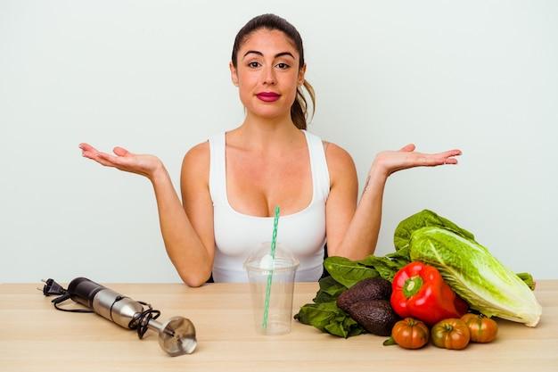 야채와 함께 건강한 스무디를 준비하는 젊은 백인 여자는 팔로 규모를 만들고 행복하고 자신감을 느낍니다.