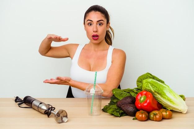 Молодая кавказская женщина готовит здоровый коктейль с овощами в шоке и изумлении, держа в руках копию пространства.