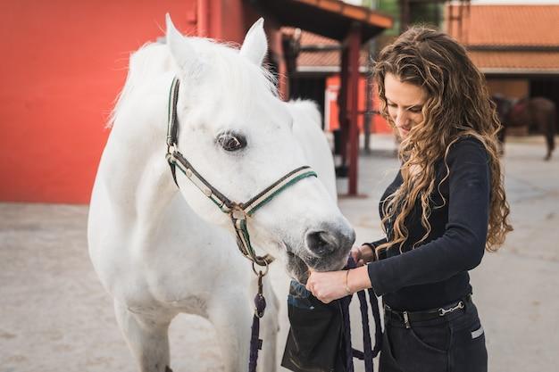 Молодая кавказская женщина готовит белую лошадь к поездке