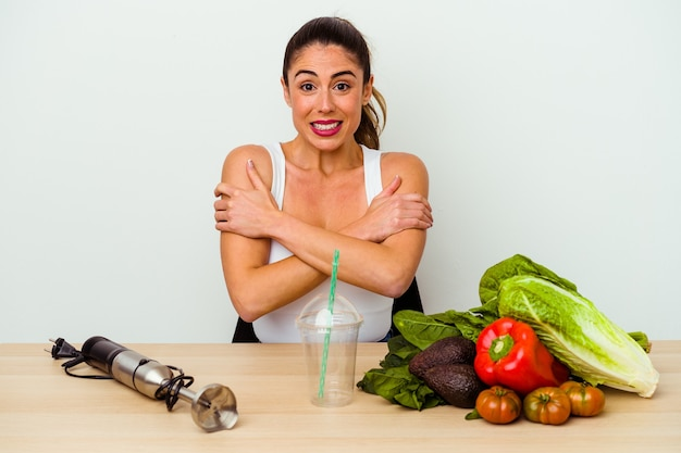 Young caucasian woman preparing a healthy smoothie with vegetables going cold due to low temperature or a sickness.