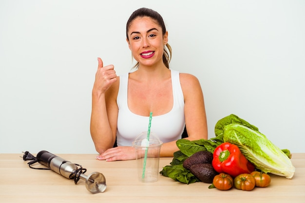Young caucasian woman preparing a healthy smoothie with vegetables smiling and raising thumb up