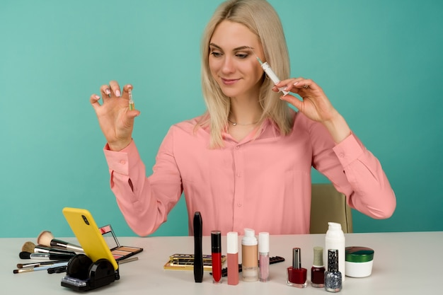 Young caucasian woman presenting beauty products while recording herself with her phone