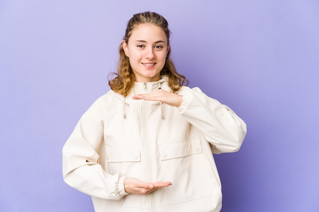 Young caucasian woman on purple holding something with both hands, product presontation.