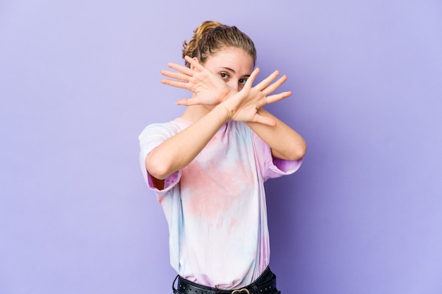 Young caucasian woman on purple space keeping two arms crossed, denial concept.
