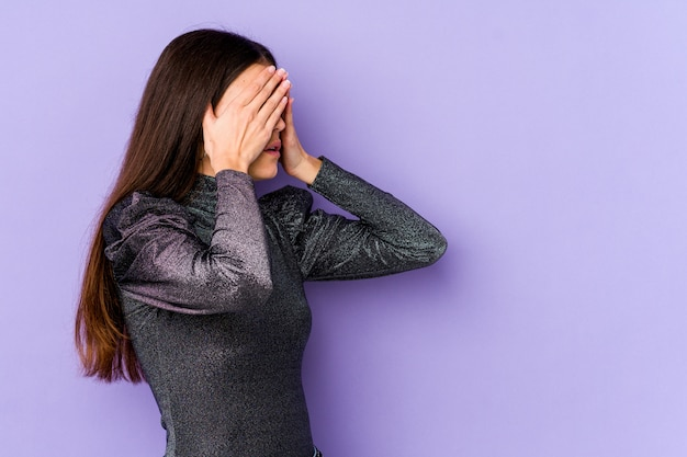 Young caucasian woman on purple wall afraid covering eyes with hands.