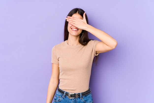 Young caucasian woman on purple wall covers eyes with hands, smiles broadly waiting for a surprise.