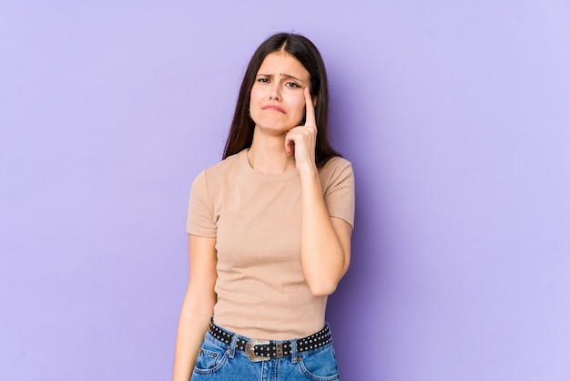 Young caucasian woman on purple wall crying, unhappy with something