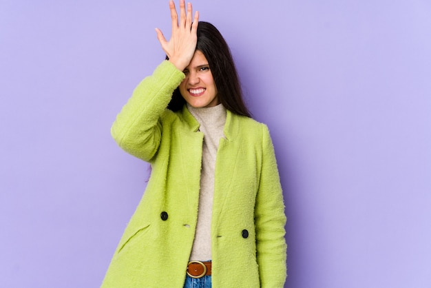Young caucasian woman on purple wall forgetting something, slapping forehead with palm and closing eyes.