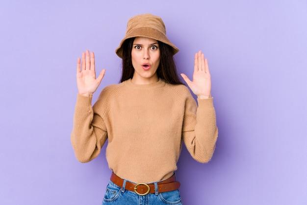 Young caucasian woman on purple wall having an idea