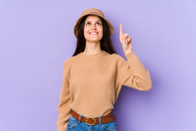 Young caucasian woman on purple wall indicates with both fore fingers up showing a blank space.
