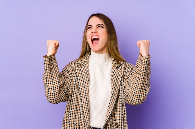 Young caucasian woman on purple wall raising fist after a victory