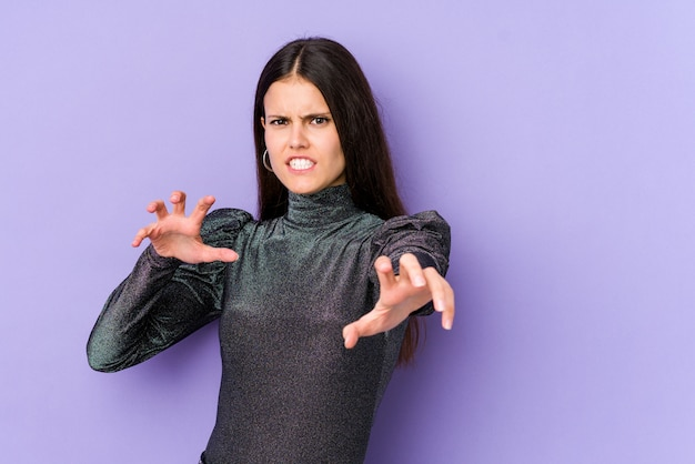 Young caucasian woman on purple wall showing claws imitating a cat