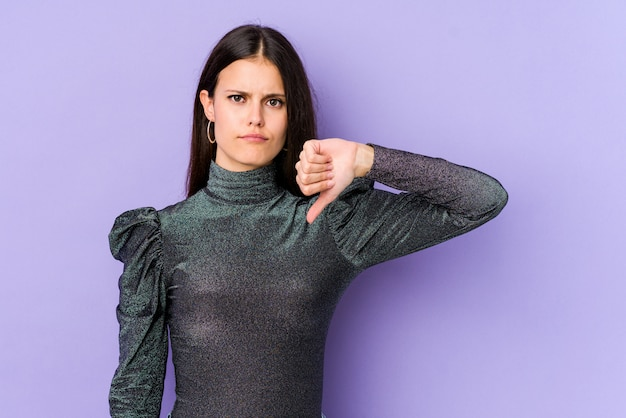 Young caucasian woman on purple wall showing thumb down