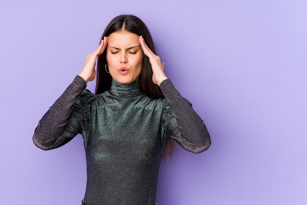 Young caucasian woman on purple wall touching temples and having headache.