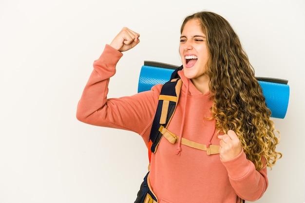 旅行の準備ができている若い白人女性は、勝利、勝者の概念の後に拳を上げて孤立しました。