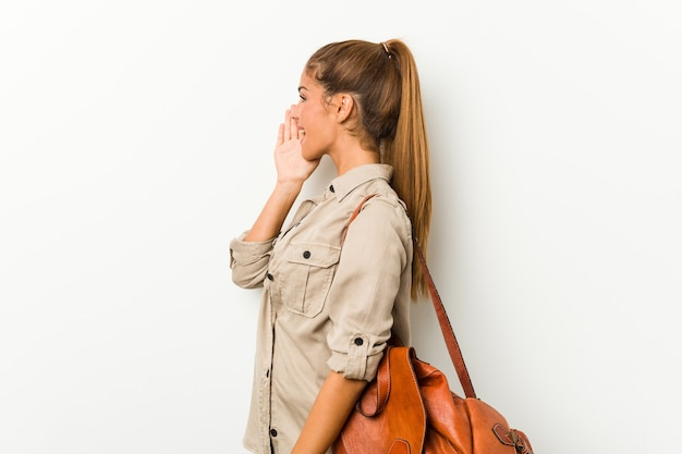 Young caucasian woman ready for a travel shouting and holding palm near opined mouth.
