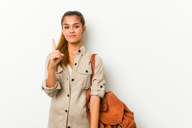 Young caucasian woman ready for a travel showing number one with finger.