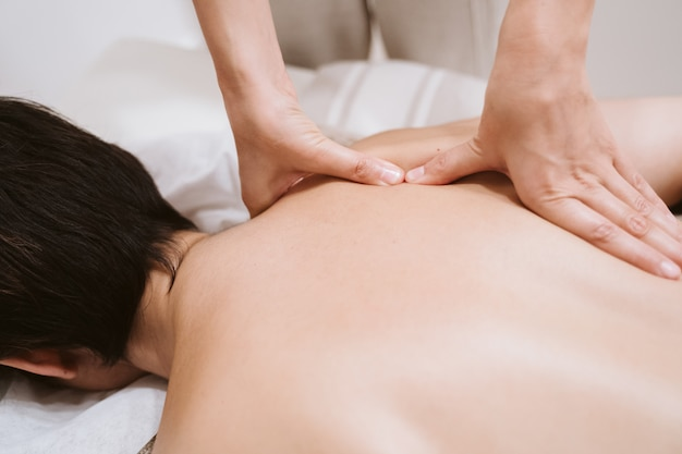 Young caucasian woman receiving back massage from physiotherapist female in clinic. physiotherapy concept