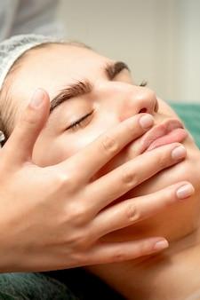 스파 의료 살롱에서 미용사의 손으로 얼굴 마사지를받는 젊은 백인 여자