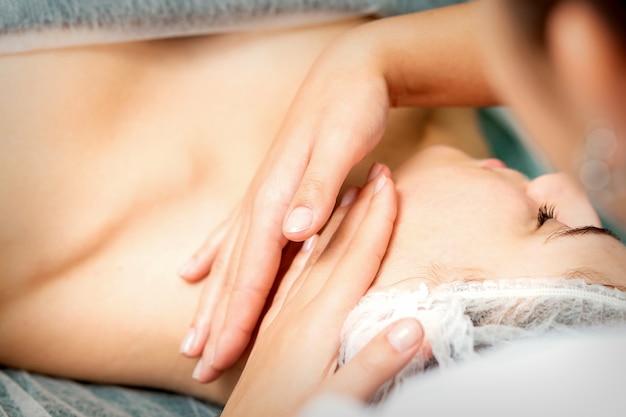 미용사에 의해 얼굴 마사지를받는 젊은 백인 여자 스파 의료 살롱에서 손