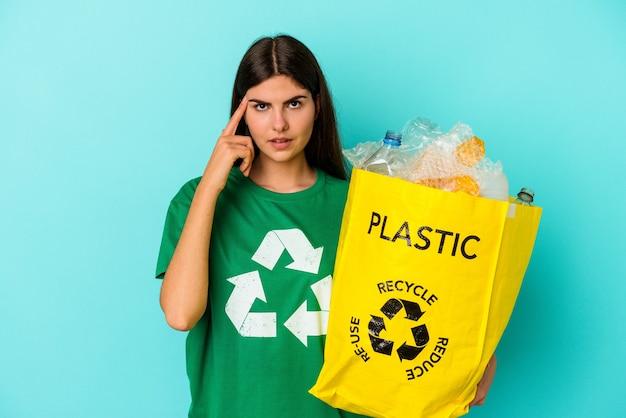 Молодая кавказская женщина переработала пластик, изолированные на синем фоне, указывая висок пальцем, думая, сосредоточившись на задаче.
