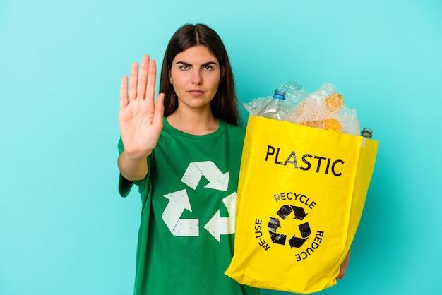 若い白人女性は、一時停止の標識を示す伸ばした手で立っている青い壁に分離されたプラスチックをリサイクルし、あなたを防ぎます