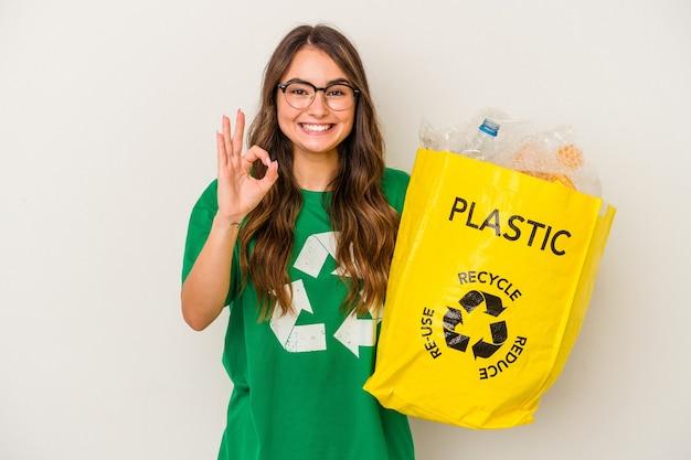 若い白人女性は、白い背景に分離されたプラスチックでいっぱいをリサイクルし、陽気で自信を持って大丈夫なジェスチャーを示しています。
