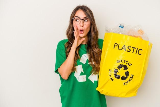 Молодая кавказская женщина, перерабатывающая пластик на белом фоне, говорит секретные горячие новости о торможении и смотрит в сторону