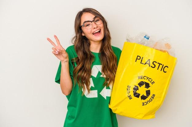 指で平和のシンボルを示す、楽しくてのんきな白い背景で隔離のプラスチックでいっぱいをリサイクルする若い白人女性。