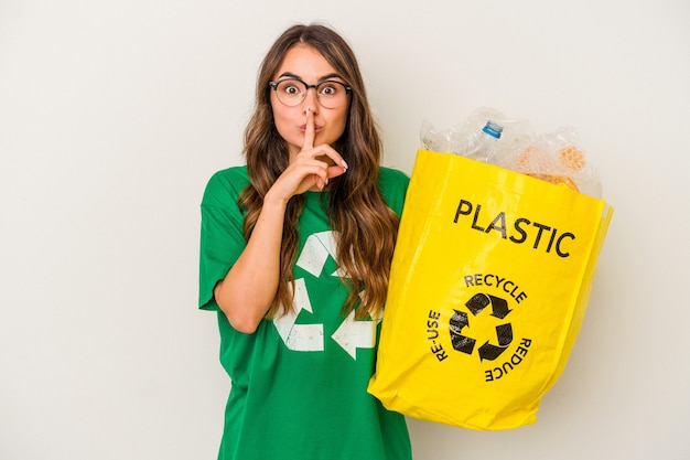 秘密を保持するか、沈黙を求めて白い背景で隔離のプラスチックでいっぱいをリサイクルする若い白人女性。