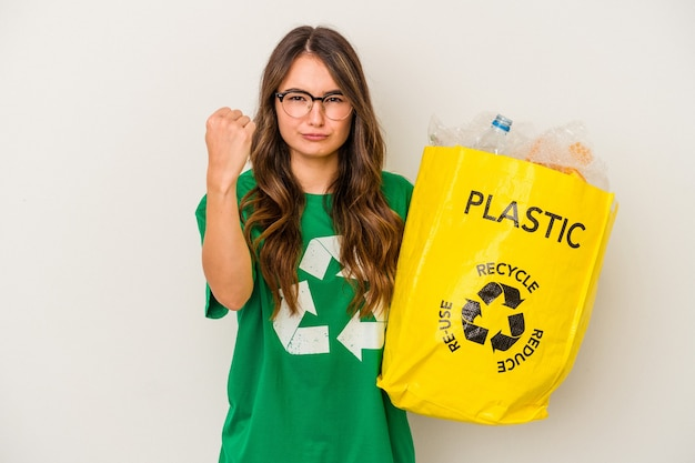 Young caucasian woman recycling a full of plastic isolated on white background  showing fist to camera, aggressive facial expression.