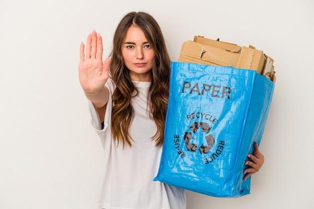 一時停止の標識を示す伸ばした手で立っている白い背景で隔離の紙をリサイクルする若い白人女性は、あなたを防ぎます。