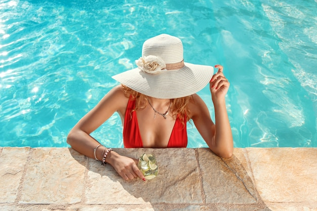 Young caucasian woman in red swimsuit and hat with tropical cocktail stain in pool