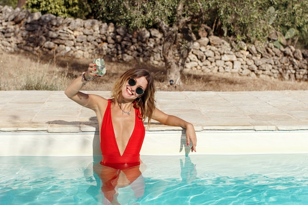 Young caucasian woman in red swimsuit relaxing near a pool with a tropical cocktail