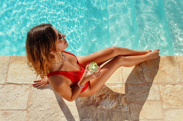 Young caucasian woman in red swimsuit with tropical cocktail relax near a pool