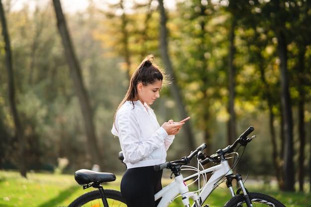 Молодая женщина кавказской, отдыхая в парке, использует мобильный телефон.