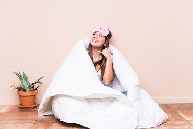 Молодая кавказская женщина, отдыхающая с лоскутным одеялом, показывая жест мобильного телефона пальцами.