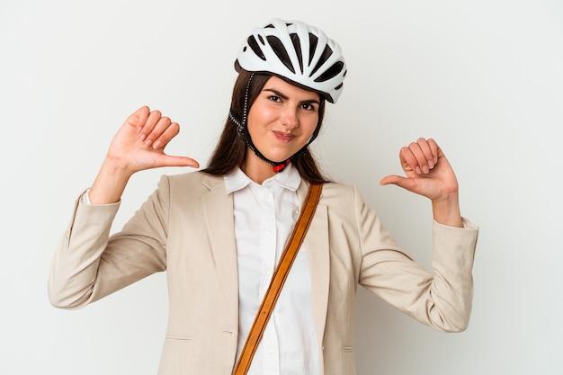 Молодая кавказская женщина, едущая на велосипеде на работу, изолирована на белом фоне, чувствует себя гордой и уверенной в себе, примером для подражания.