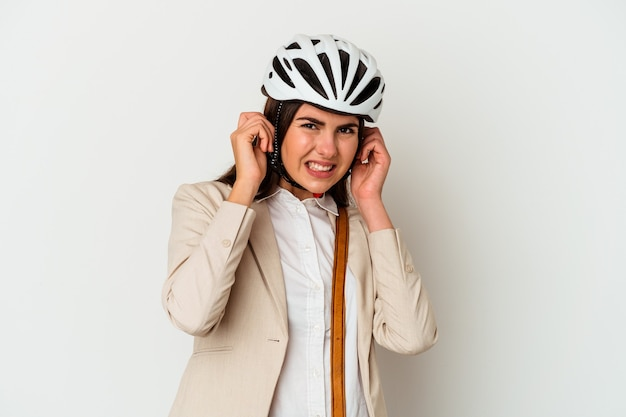 Young caucasian woman riding a bicycle to work isolated on white background covering ears with hands.