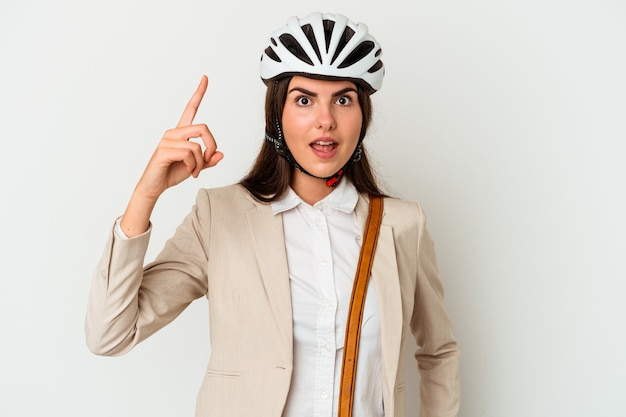 Young caucasian woman riding a bicycle to work isolated on white background having an idea, inspiration concept.