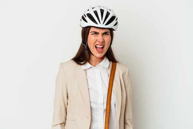Young caucasian woman riding a bicycle to work isolated on white background screaming very angry and aggressive.