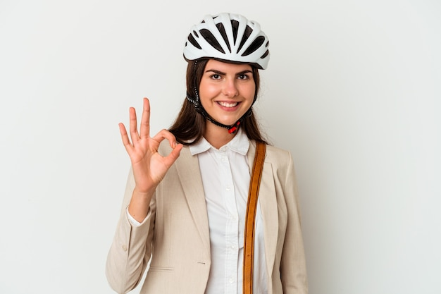 Young caucasian woman riding a bicycle to work isolated on white wall cheerful and confident showing ok gesture