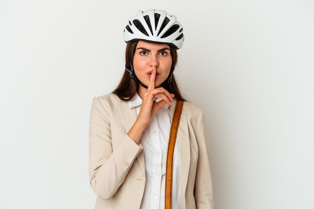 Young caucasian woman riding a bicycle to work isolated on white wall keeping a secret or asking for silence