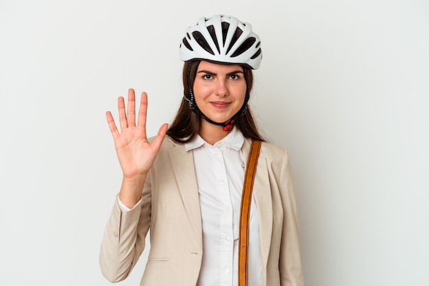 Young caucasian woman riding a bicycle to work isolated on white wall smiling cheerful showing number five with fingers