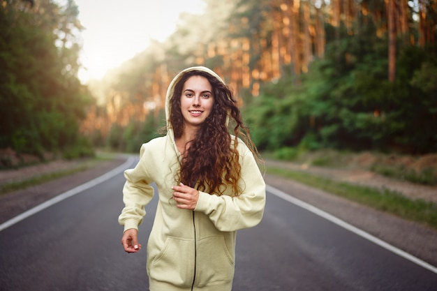 Молодая кавказская женщина работает асфальтированная дорога солнечное летнее утро