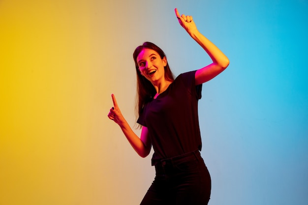 Young caucasian woman's portrait on gradient blue-yellow studio background in neon light. concept of youth, human emotions, facial expression, sales, ad. beautiful brunette model.